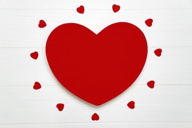 Большое красное сердце и много маленьких сердец на белой деревянной доске как романтический фон. день святого валентина, женский день, поздравительная открытка дня матери или приглашение на свадьбу с копией пространства.