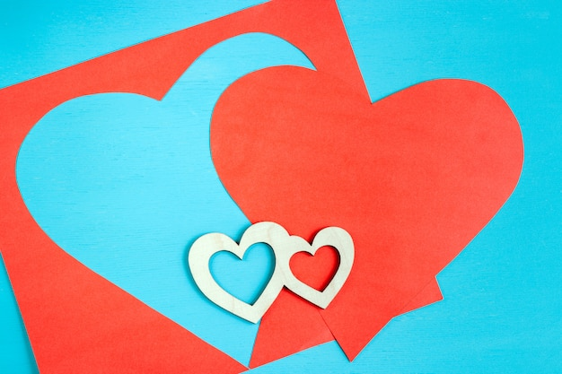 Big red heart carved from paper sheet and two small wooden hearts are lying on bright azure.