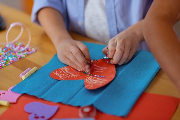 큰 붉은 마음. 수업에서 큰 붉은 마음으로 적용된 장식을 만드는 남학생의 닫습니다