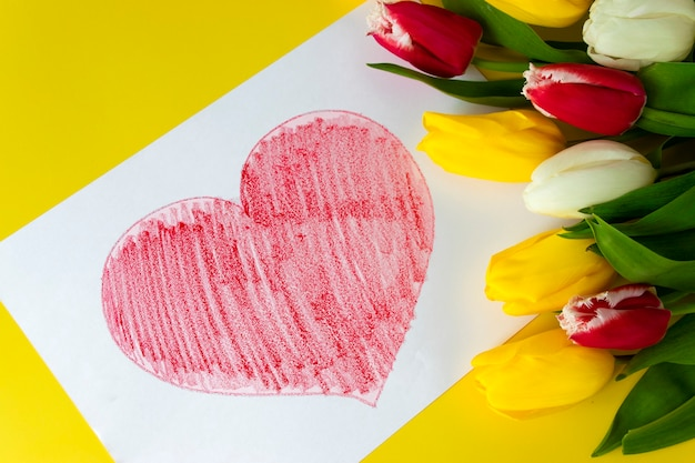 Big red heart drawn on paper and bouquet of flowers colorful tulips on yellow