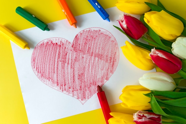 Big red heart drawn on paper crayons pencils and bouquet of flowers colorful tulips on yellow