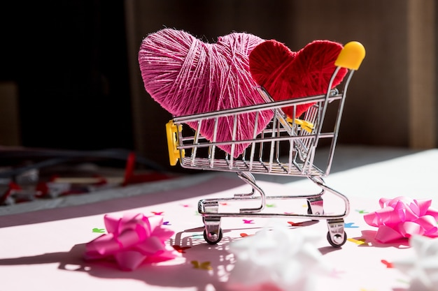 Большое красное сердце в корзине. концепция покупки любви. день святого валентина. интернет-магазины. тележка с сердечками.