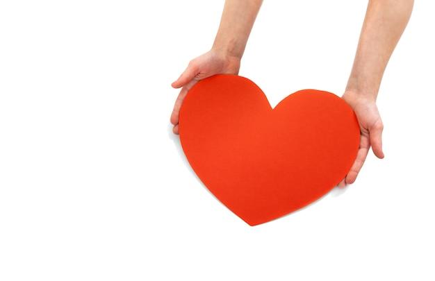 白い背景の上の子供の手の大きな赤いハート。バレンタインデーの空白のグリーティングカード、テキスト用の空きスペース。