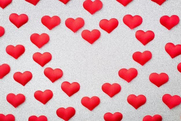 Большое красное сердце из множества более мелких на серебряном фоне