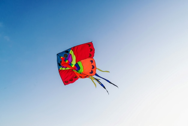 Big red kite in clear blue sky