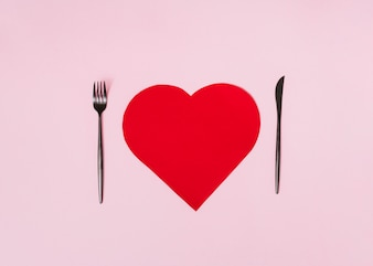 Big red paper ornament heart between cutlery