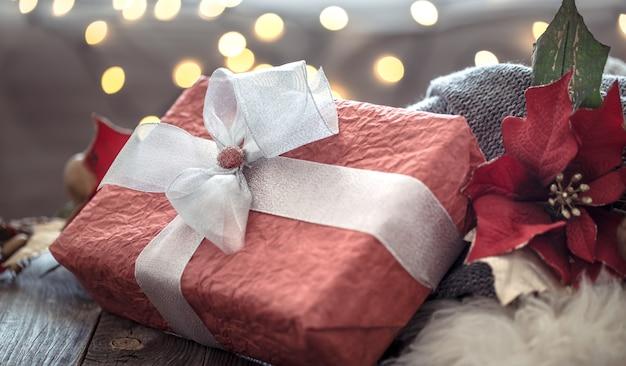 Grande rosso presente sopra le luci di natale bokeh in casa sulla tavola di legno. decorazione natalizia, magico natale