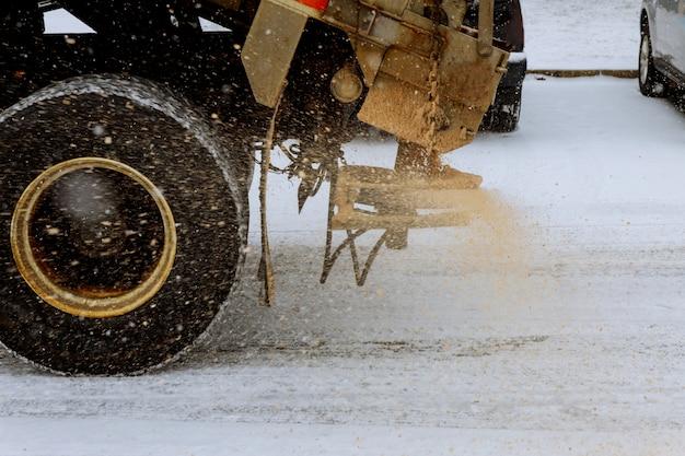 降雪と氷の間に大きな赤い除雪車の砂車道