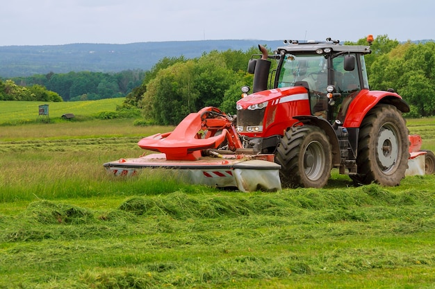A big red tractor with two mowers mows the green grass on a silo.