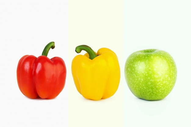 Big red and yellow peppers and big green apple