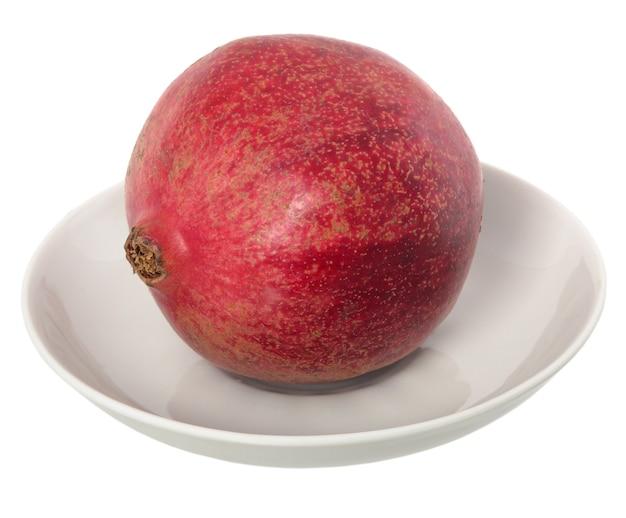 白いプレートに大きな熟した赤いグラネットまたはガーネット。白い背景の上の赤い熟したザクロの果実。ベジタリアンコンセプト、有機ビタミン、デトックス、ダイエット。