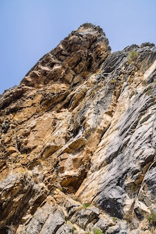 Big rocky mountain cliff under blue sky close-up