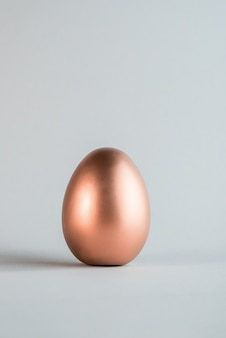 Big rose gold color easter egg on a simple gray background.