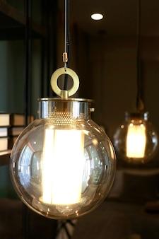 リビングルームを飾るために天井からぶら下がっている大きな丸いレトロなスタイルの電球