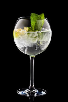 Big round wine glass with fresh cold lemonade isolated on black background
