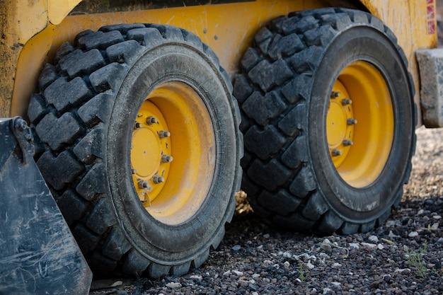 Большие резиновые колеса сельскохозяйственного трактора, стоя на фоне полевой дороги. крупным планом снимок грязного колеса погрузчика. выборочный фокус. трактор с грязным колесом. старые колеса экскаваторной машины.
