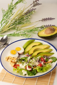 The big salad consists of sliced avocado, boiled egg, lettuce, lettuce, tomato and biscuits, topped with salad cream, avocado cut in half on the back, a meal with a lot of vegetables.