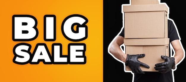 큰 판매 배너입니다. 검은 배경에 상자를 들고 남성 배달 택배