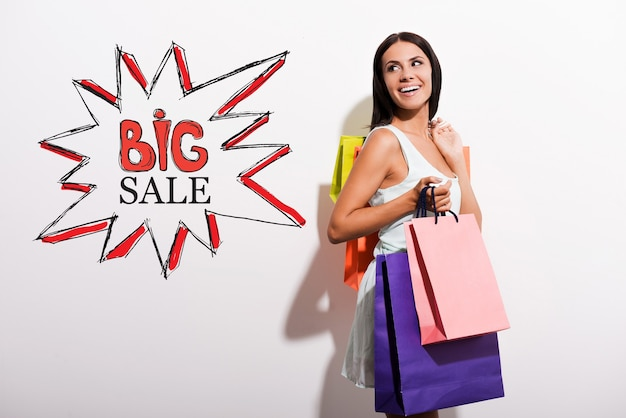 Big sale! happy young woman in dress carrying colorful shopping bags and looking over shoulder