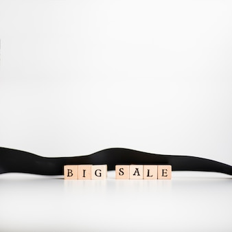 Big sale inscription on wooden blocks with ribbon