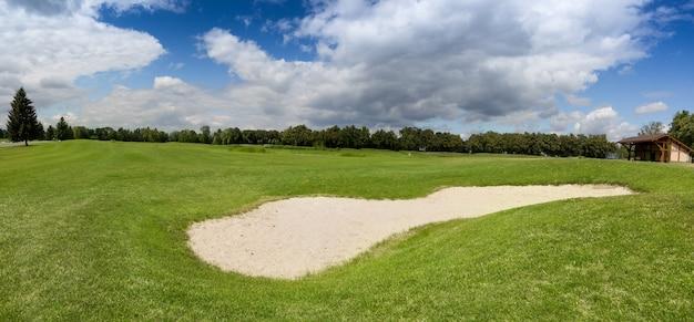 完璧な緑の芝生のあるゴルフコースの大きな砂のバンカー
