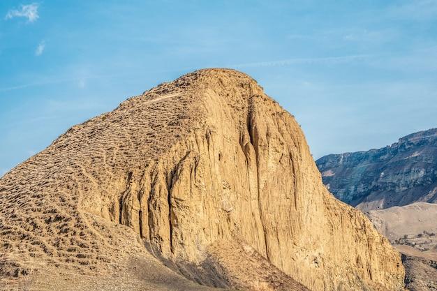 大きな砂の山。美しい砂漠の風景、砂と石の間に青い空を背景に大きな山があります。