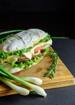 Big sandwich on black rosemary cucumber wooden board green onion