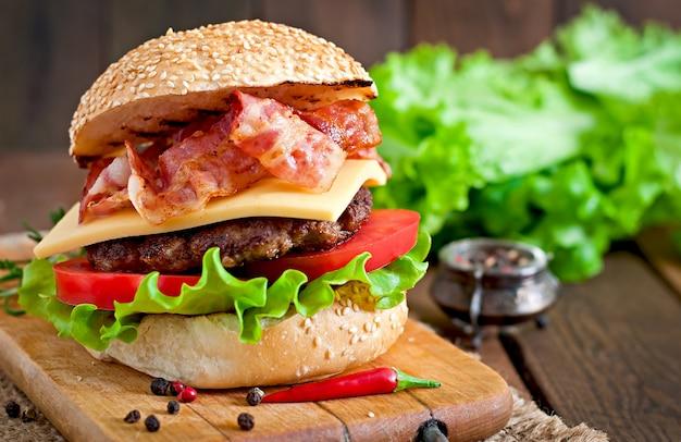 큰 샌드위치-쇠고기, 치즈, 토마토, 튀긴 베이컨이 들어간 햄버거 버거