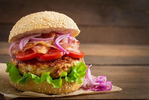 Большой бутерброд - гамбургер с говядиной, красным луком, помидорами и жареным беконом.