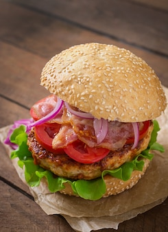 Big sandwich - hamburger burger with beef, red onion, tomato and fried bacon.