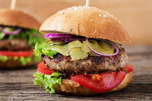 大きなサンドイッチ-牛肉、トマト、チーズ、キュウリのピクルスのハンバーガーバーガー。