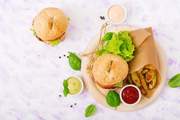 Большой сэндвич - гамбургер с сочным говяжьим гамбургером, сыром, помидорами, красным луком и картофелем фри. вид сверху. плоская планировка