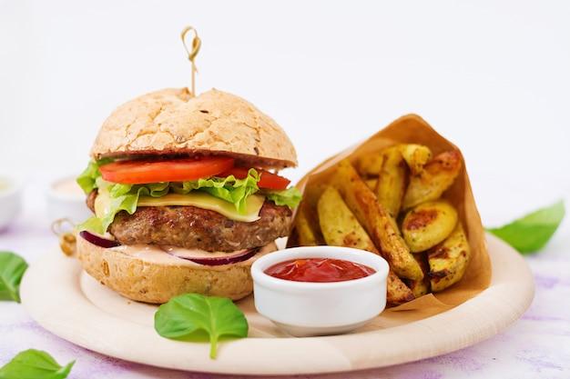 Большой сэндвич - гамбургер с сочным говяжьим гамбургером, сыром, помидорами, красным луком и картофелем фри.