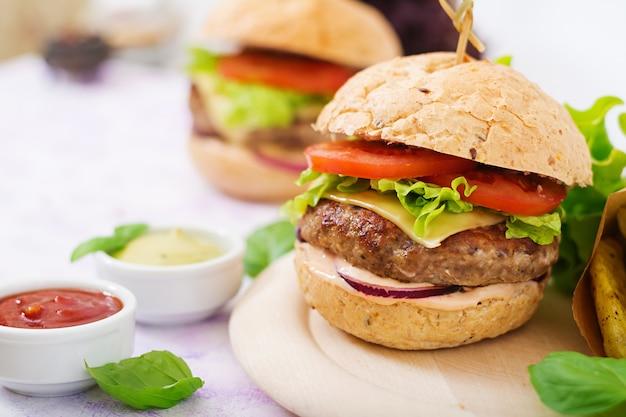 큰 샌드위치-수분이 많은 쇠고기 버거, 치즈, 토마토, 붉은 양파와 감자 튀김이 들어간 햄버거.