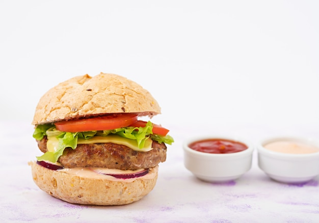 Big sandwich - hamburger with juicy beef burger, cheese, tomato, and red onion on light table and french fries.