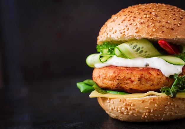 Big sandwich - hamburger with juicy chicken burger, cheese, cucumber, chili and tartar sauce on black background