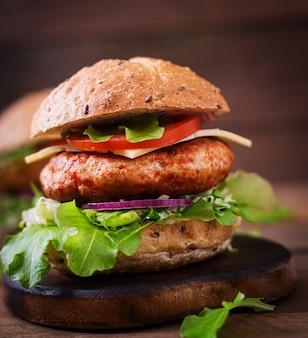 Большой бутерброд - гамбургер с сочным куриным бургером, сыром, помидорами и красным луком на деревянном столе