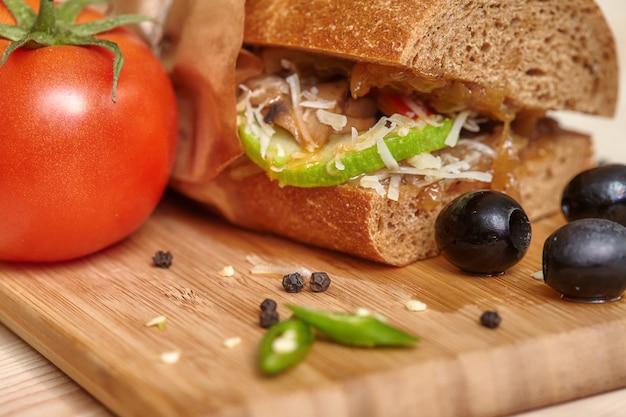 Большой бутерброд на деревянной разделочной доске с ингредиентами