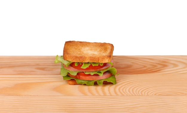 Big sandwich with fresh vegetables on wooden board on white wall