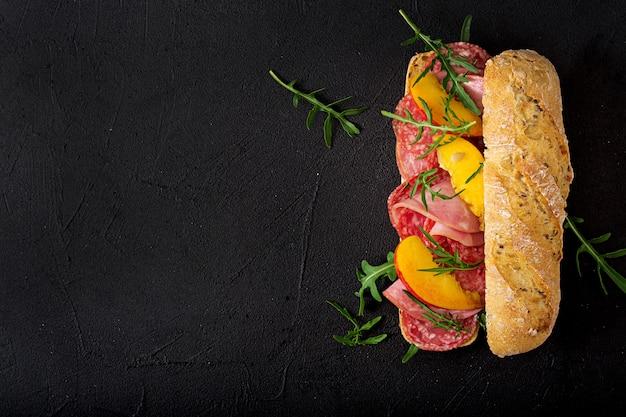Большой бутерброд с ветчиной, салями, нектарином и рукколой. квартира лежала. вид сверху