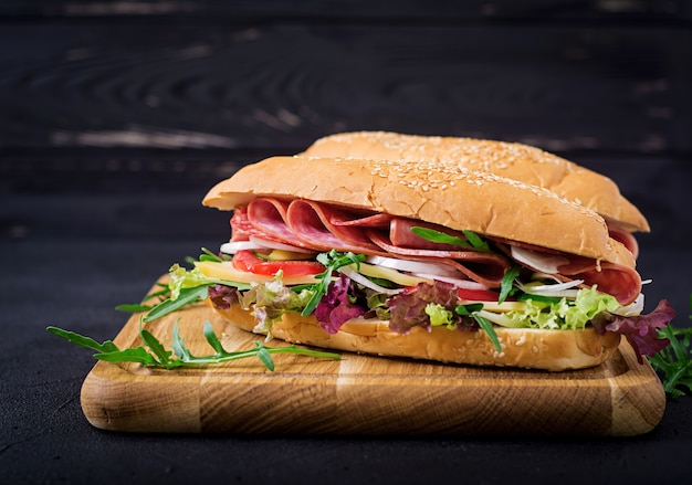 Big sandwich with ham, salami, tomato, cucumber and herbs