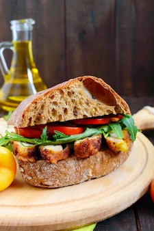 Big sandwich with pieces of meat, arugula, tomato, cereal ciabatta on cutting board on dark wooden table