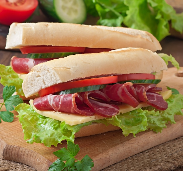 Big sandwich with raw smoked meat on a wooden background