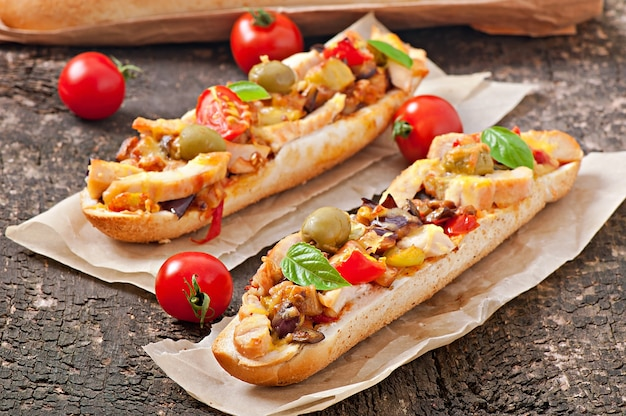 Big sandwich with roasted vegetables and chicken with cheese and basil on old wooden surface