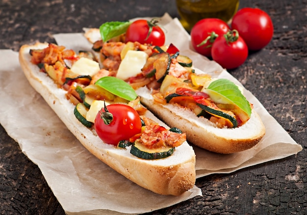 Big sandwich with roasted vegetables with cheese and basil on old wooden surface