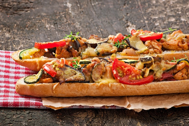 Big sandwich with roasted vegetables (zucchini, eggplant, tomatoes) with cheese and thyme on old wooden background