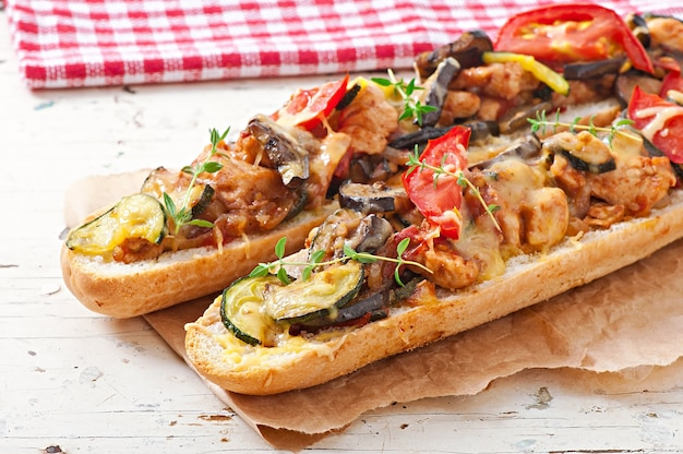 Big sandwich with roasted vegetables (zucchini, eggplant, tomatoes) with cheese and thyme