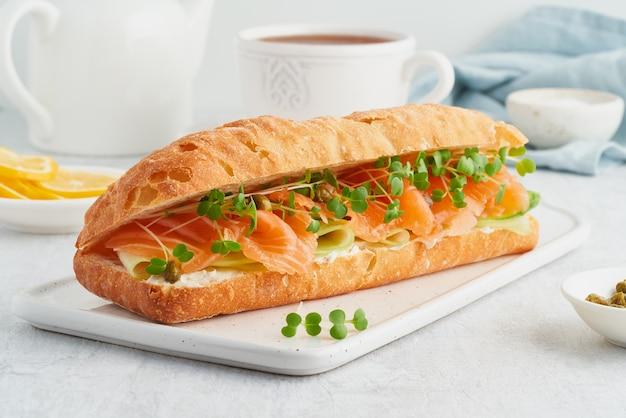 Big sandwich with salmon cream cheese cucumber slices on white concrete table