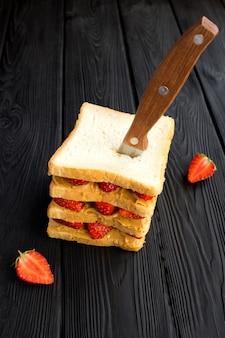 黒い木製の背景にイチゴとピーナッツバターの大きなサンドイッチ。垂直位置。