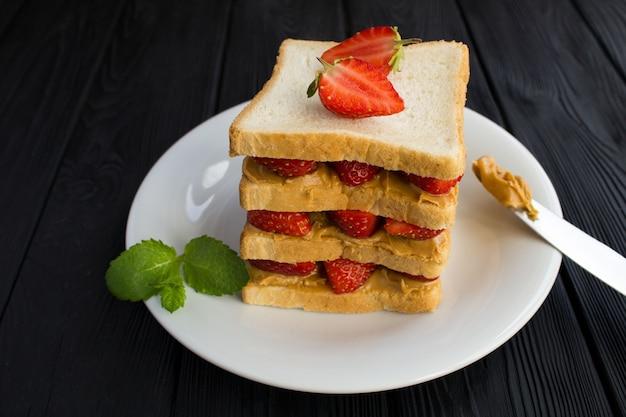 黒い木製のテーブルの白いプレートにイチゴとピーナッツバターの大きなサンドイッチ